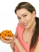 Vonzó fiatal nő, egy maroknyi hagyma gazdaság ízű ételek gyűrű