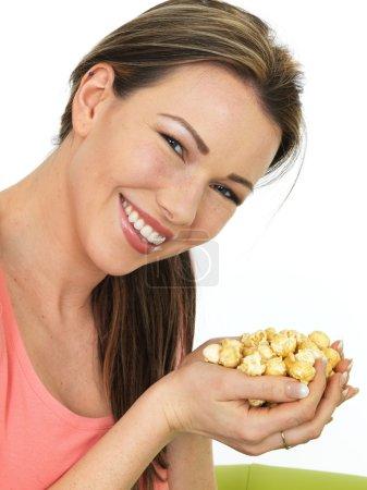 attraktive junge glückliche Frau mit einer Handvoll mit Toffee beschichtetem Popcorn