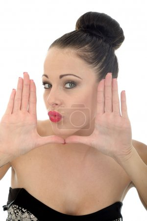Young Woman Framing Her Face With Her Hands Looking Happy and Pleased