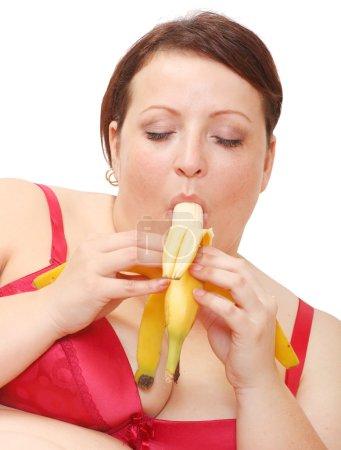 Overweight woman eating sweet banana.