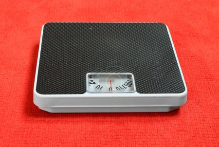 Photo pour Retro style weighing machine on a red background. - image libre de droit