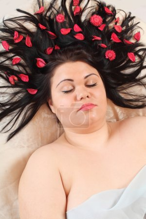 Overweight woman relaxing with petals in hair