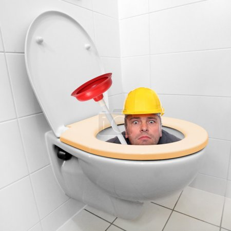 Photo pour Réparateur drôle regardant de la cuvette de toilette. - image libre de droit
