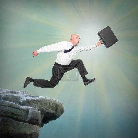 Photo pour Homme d'affaires sénior sautant d'un bord de falaise. Métaphore carrière et assurance . - image libre de droit