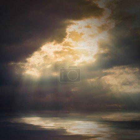 The sun on dramatic sky over sea.