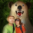 Selfie of funny backpackers couple with bear frien...