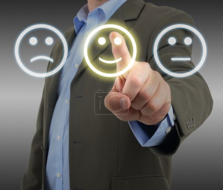 Photo for Like us. Man in suit choosing a smiley face on a survey panel - Royalty Free Image