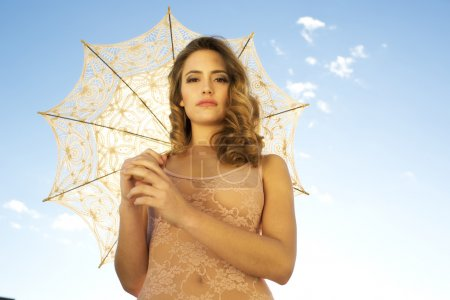 pretty face of woman outside under sun umbrella