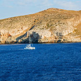 sailing  near hill and rocks on the summertime beach in europe g