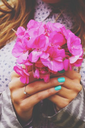 Photo for Stylish lady holding bunch of pink flowers in her hands with teal manicure - Royalty Free Image