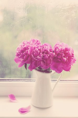 Bouquet of pink peonies on a windowsill, vintage effect