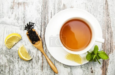 Photo for Cup of tea with lemon and mint on wooden background - Royalty Free Image
