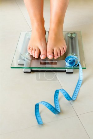 Woman feet standing on bathroom scale and tape measure