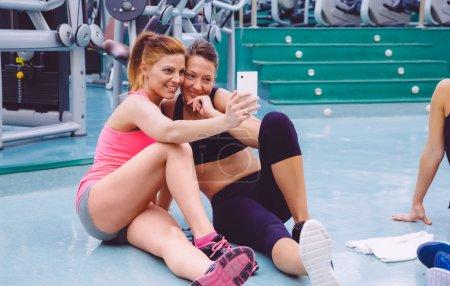 Photo pour Jeunes belles amies prenant un selfie avec smartphone assis sur le sol d'un centre de fitness après une dure journée d'entraînement - image libre de droit