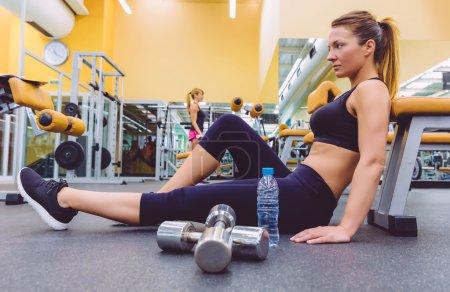 Photo pour Belle femme sportive se reposant s'asseyant sur le plancher du centre de forme physique et de l'ami féminin faisant des exercices avec des haltères à l'arrière-plan - image libre de droit