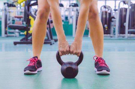 Photo pour Gros plan de belle femme prête à soulever kettlebell en fer noir dans un entraînement crossfit sur le centre de fitness - image libre de droit