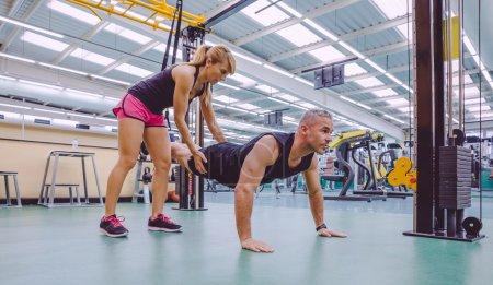 Photo pour Entraîneur personnel féminin enseignant à l'homme dans un entraînement de suspension dure avec des sangles de fitness sur un centre de fitness - image libre de droit