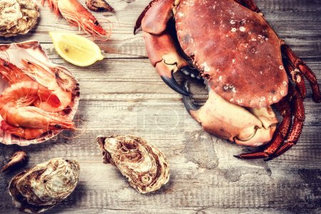 Photo for Steamed crab, shrimps and fresh oysters on wooden background. Sea food dinner concept - Royalty Free Image