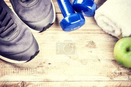 Photo pour Cadre de fitness avec haltères, baskets et pomme verte. Concept de mode de vie sain avec espace de copie - image libre de droit
