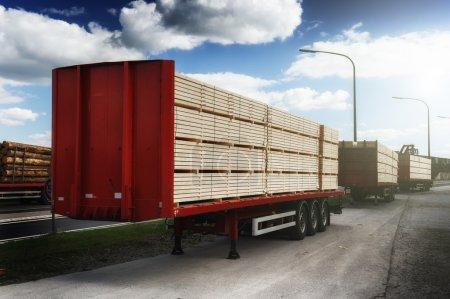 Photo pour Camions chargés de planches de bois en attente pour la livraison - image libre de droit