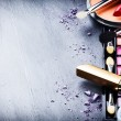 Various makeup products on dark background with co...