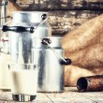 Farm setting with fresh milk in various bottles an...