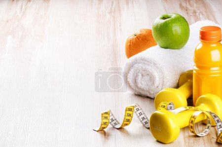 Photo for Fitness concept with dumbbells and fresh fruits. Workout setting - Royalty Free Image