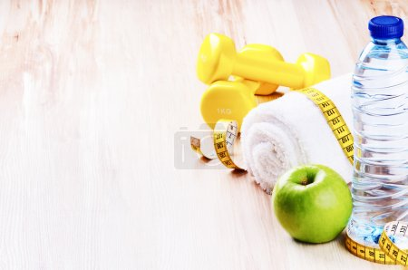 Dumbbells, green apple and water bottle