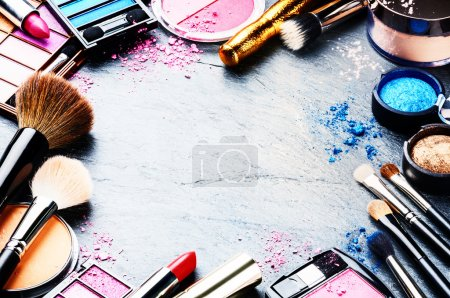 Colorful frame with various makeup products on dar...