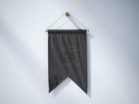 Photo pour Pennant noir accroché à un mur en béton - image libre de droit