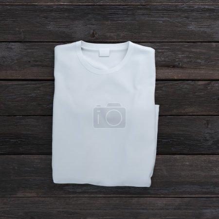 White folded t-shirt on wooden background