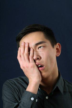 Asian man showing facepalm
