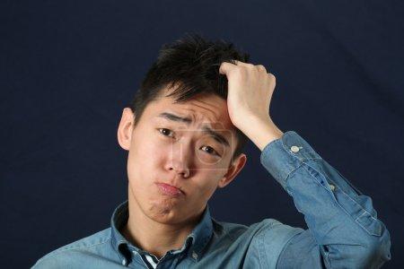 Photo pour Déçu jeune homme asiatique faisant visage et regardant la caméra - image libre de droit