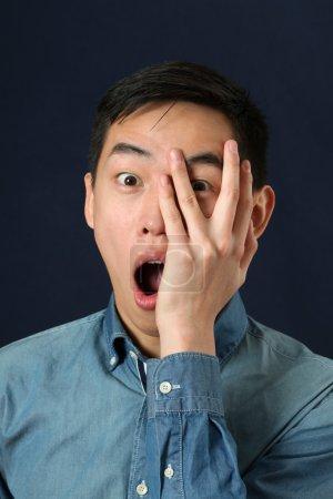 Asian man looking through  fingers