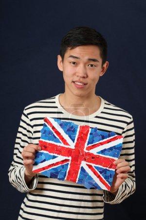 Photo pour Jeune étudiant asiatique montrant le drapeau national du Royaume-Uni et regardant la caméra - image libre de droit