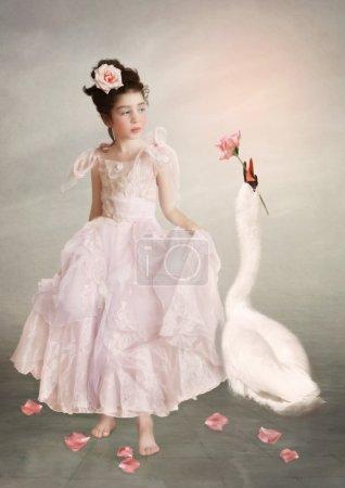 Photo pour Petite fille en robe longue rose avec fleur rose dans les cheveux et cygne blanc - image libre de droit