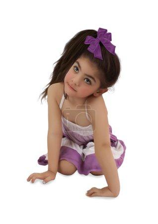 Photo pour Petite fille avec arc violet assis sur ses hanches et regarde vers le haut surprise sur fond blanc - image libre de droit