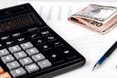 Obchodní grafy s kalkulačka, peníze a pera