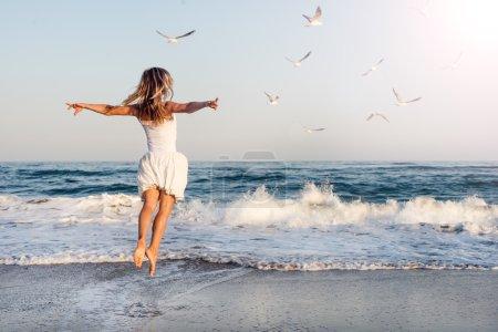 Photo pour Belle jeune fille volant avec des mouettes sur la mer - image libre de droit
