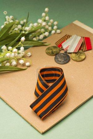 Photo pour Jour de la Victoire. Ruban St. George, médailles et lys de vallée - image libre de droit