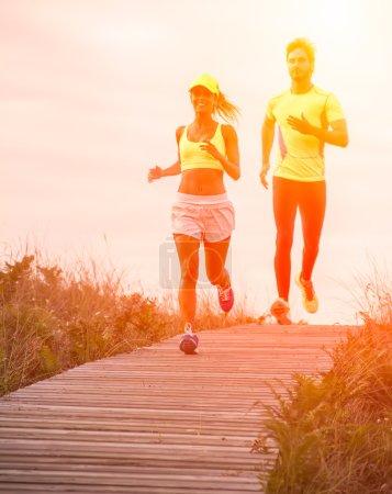 Photo pour Jeunes coureurs de couple s'entraînant sur la plage - image libre de droit