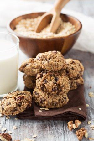 Photo pour Biscuits à l'avoine croquants faits maison avec du chocolat noir et un verre de lait sur un fond en bois blanc, mise au point sélective - image libre de droit