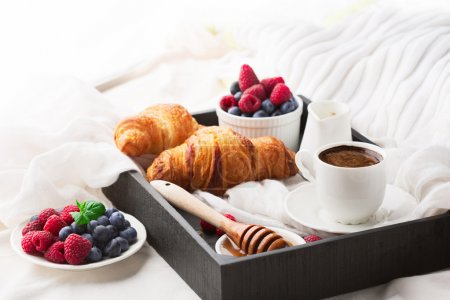 Photo for Morning breakfast in bed with cup of coffee, croissants, fresh berries and honey on wooden tray, selective focus - Royalty Free Image