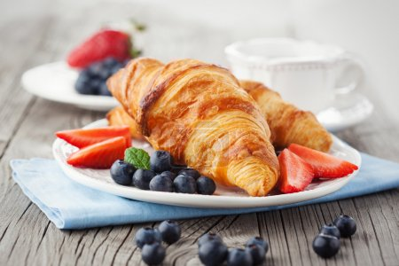 Photo for Delicious breakfast with fresh croissants and ripe berries on old wooden background - Royalty Free Image