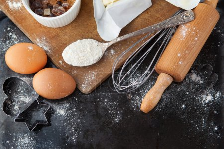 Photo for Baking background with raw eggs, rolling pin, flour and cookie cutters on black chalkboard - Royalty Free Image