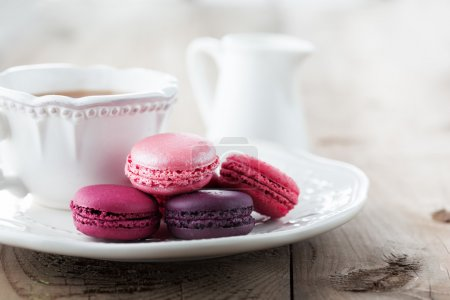 Photo for Colorful French macaroons and cup of tea on a rustic wooden background, selective focus - Royalty Free Image