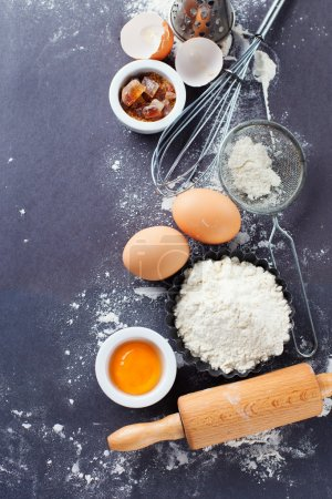 Photo for Ingredients and tools for baking - flour, eggs and rolling pin on the black background, top view - Royalty Free Image