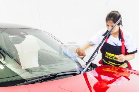 Photo pour Nonthburi, Thaïlande - 26 mars 2015 : Un ouvrier nettoie le pare-brise de Porsche 911 Carrera 4 GTS, une voiture aux performances exceptionnelles, a montré en Thaïlande le 36ème Salon International de Bangkok le 26 mars 2015 - image libre de droit