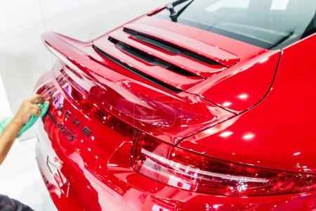 Photo pour Nonthburi, Thaïlande - 26 mars 2015 : Un travailleur nettoie l'arrière de Porsche 911 Carrera 4 GTS, une voiture aux performances exceptionnelles, a présenté en Thaïlande le 36e Salon international de l'automobile de Bangkok le 26 mars 2015 - image libre de droit