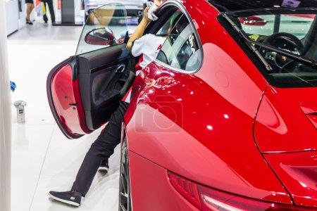 Photo pour Nonthburi, Thaïlande - 26 mars 2015 : Nettoyage des travailleurs à l'intérieur de Porsche 911 Carrera 4 GTS, une voiture de performance exceptionnelle, a montré en Thaïlande le 36e Salon international de l'automobile de Bangkok le 26 Mars 2015 - image libre de droit